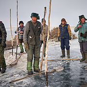 """Buryati ice fishermen try to catch fish on the ice for food at Russia's Lake Baikal. <br /> <br /> After decades of overfishing by the fishing industry, Baikal is running out of fish, and locals are bearing the consequence. <br /> <br /> Crowned the """"Jewel of Siberia"""", Baikal is the world's deepest lake, and the biggest lake by volume, holding 20% of the world's fresh water. In the winter, the lake 31,722 square meter surface is entirely frozen with ice averaging 2 meters thick. Its ecology is one of the world's most critical."""