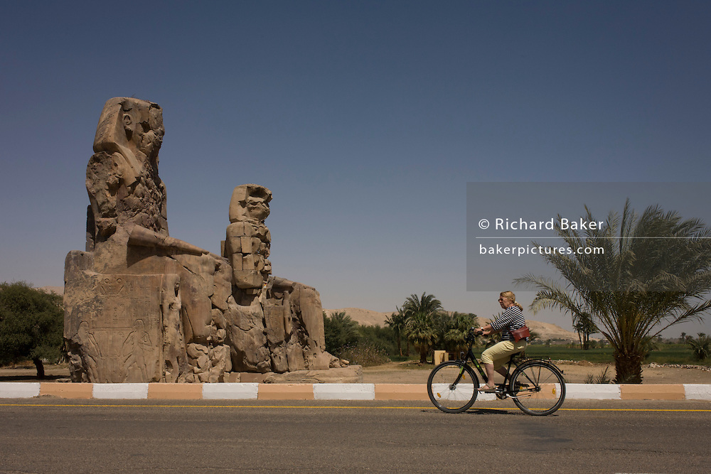 A tourist on rented bikes cycles past the ancient Egyptian Colossi of Memnon site, Luxor, Nile Valley, Egypt. The Colossi of Memnon (memorial temple of Amenophis III) are two massive stone statues of Pharaoh Amenhotep III, who reigned during Dynasty XVIII. For the past 3,400 years (since 1350 BC) they have stood in the Theban necropolis, west of the River Nile from the modern city of Luxor.