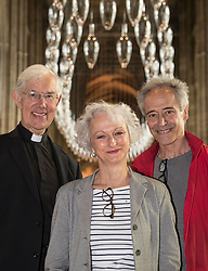 © Licensed to London News Pictures. 24/05/2018. Canterbury, UK. Artists artists Philip Baldwin (R) and Monica Guggisberg stand with Very Revd Dr Robert Willis at Canterbury Cathedral. A series of glass installations by the artists reflecting on themes of war and remembrance, migration and refugees are going on display at the cathedral commemorating the 100th anniversary of the end of the First World War. Under an Equal Sky will take visitors on a journey that begins with the Boat of Remembrance in the Nave and ends with a glass wall of multi-coloured vessels in The Crypt . Photo credit: Peter Macdiarmid/LNP