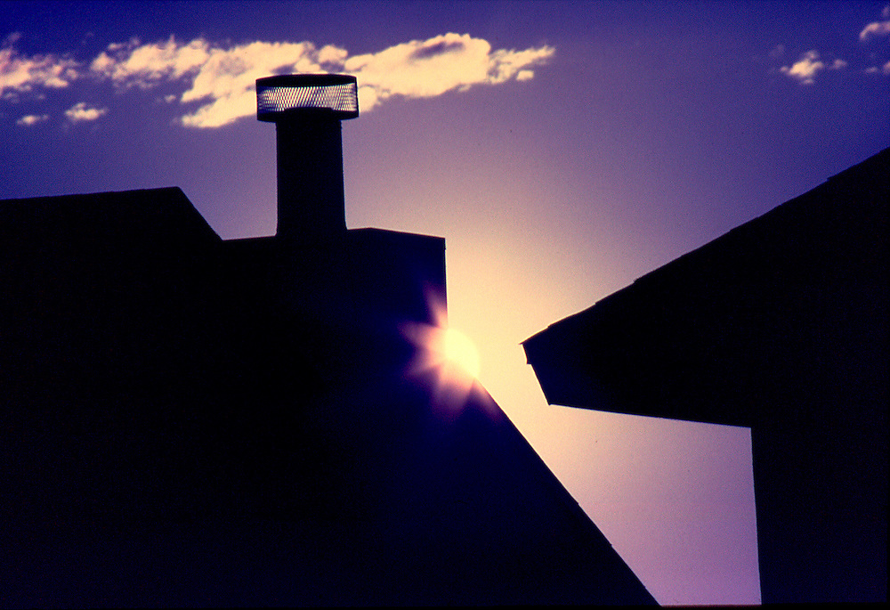 Abstract , sunrise over home roof tops .