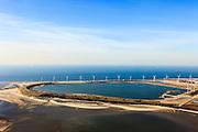 Nederland, Rotterdam, Maasvlakte, 20-03-2009; De Slufter, grootschalige opslagplaats voor vervuild havenslib. De verontreinigde baggerspecie komt voort uit het onderhoudsbaggerwerk in de Rotterdamse haven waarbij de haven op diepte wordt gehouden. Langs de rand van de Slufter zijn windmolens gebouwd en in de Noordzee, direkt links naast het depot, wordt de Tweede Maasvlakte aangelegd. Slufterstrand (Strand Slufter) in de voorgrond.<br /> The Slufter, large-scale storage for contaminated harbor sludge.<br /> luchtfoto (toeslag op standard tarieven);<br /> aerial photo (additional fee required);<br /> copyright foto/photo Siebe Swart