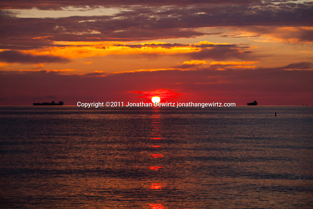 The sun rises on the horizon off Miami Beach as cargo ships wait to dock. WATERMARKS WILL NOT APPEAR ON PRINTS OR LICENSED IMAGES.