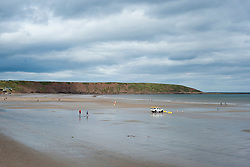 As the calm blue sea of Filey Bay recedes and RNLI Beach Life Guard  vehicle sits on the sand people return to the beach
