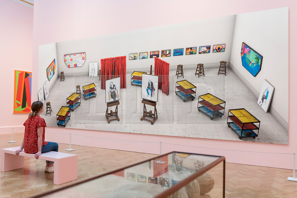 """© Licensed to London News Pictures. 05/06/2018. LONDON, UK. A staff member views """"Seven Trollies, Six and a Half Stools, Six Portraits, Eleven Paintings and Two Curtains"""" by David Hockney RA at a preview of the 250th Summer Exhibition at the Royal Academy of Arts in Piccadilly, which has been co-ordinated by Grayson Perry RA this year.  Running concurrently, is The Great Spectacle, featuring highlights from the past 250 years.  Both shows run 12 June to 19 August 2018.  Photo credit: Stephen Chung/LNP"""
