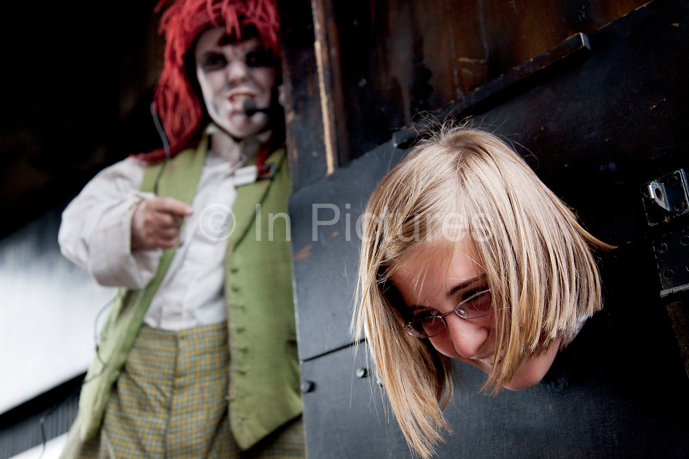 Dwarf dressed up in horror make up and period clothing at London Dungeons (London Bridge Experience) performs a mock execution on a tourist who stops and requests to have her head cut off in a fake guillotine. The London Bridge Experience and The London Tombs are two gruesome London tourist attractions. This themed attraction takes tourists on a journey through the history of this exciting area of London, from the Roman invasion, right up to the present day. See, hear, feel, taste, even smell, what London Bridge was like over the ages.