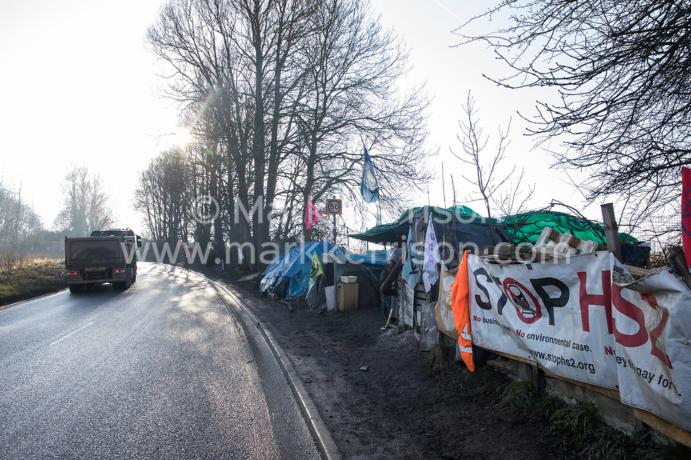 Harefield, UK. 21 January, 2020. A truck passes the roadside site of the Save the Colne Valley Stop HS2 wildlife protection camp on Harvil Road. Activists reoccupied the field behind the roadside camp on 18th January in order to seek to protect ancient woodland set to be destroyed by HS2.