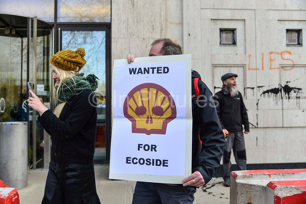 A woman films protesters on her phone outside the Shell oil HQ on 15th April 2019 in London, United Kingdom.  Extinction Rebellion a climate change protest group are protesting  across the centre of London and plan to block traffic for the next five days.