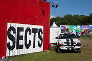 """Glastonbury Festival, 2015. Shangri La is a festival of contemporary performing arts held each year within Glastonbury Festival. The theme for the 2015 Shangri La was Protest.  Building the Shangri La field. Painting the word """"SECTS"""" on the Shangri-Hell headquarters."""