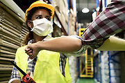 Two colleague female and male workers in warehouse factory have a greeting by touching the elbow or elbow bump to prevent the COVID infection. All people wear mask in industrial workplace for health.