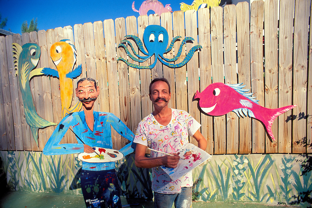 Artist, teacher, and activist Stewart Stewart with a self-portrait plus cut-out, wooden sculptures he made of fish and various other creatures on a wall at his South Beach home.