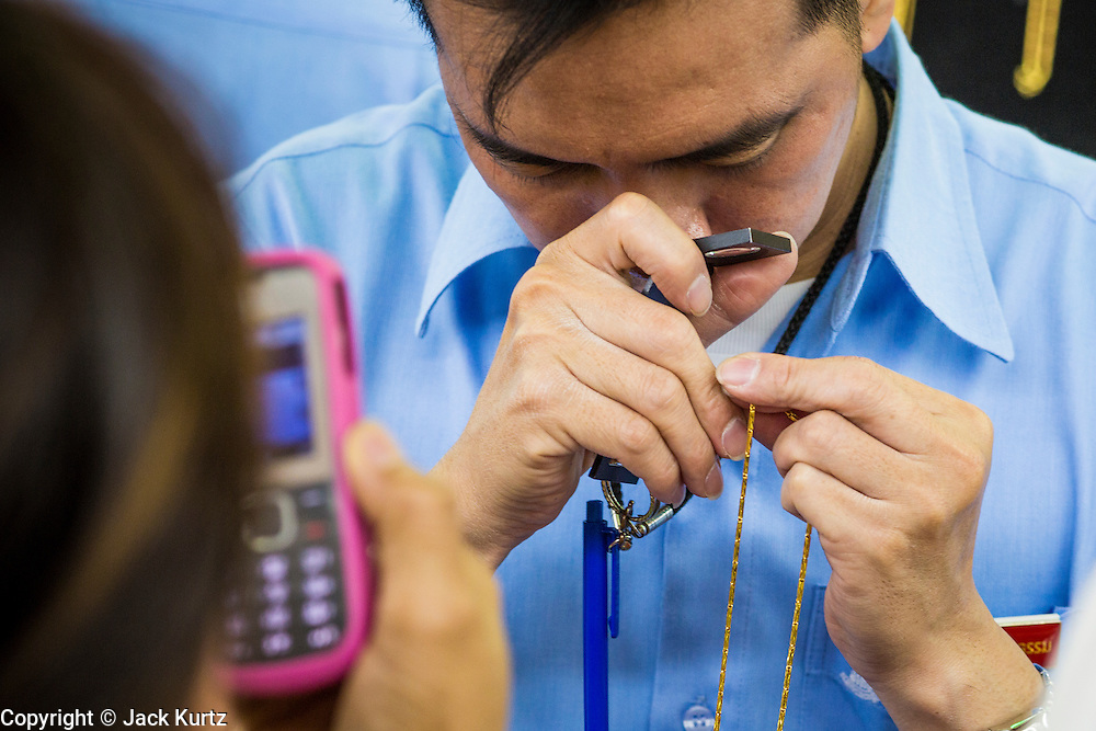 17 APRIL 2013 - BANGKOK, THAILAND:  A salesman in a gold shop evaluates a gold necklace for a customer. Thais flocked to gold shops in Bangkoks's Chinatown this morning to buy gold. Wednesday was the first day most gold shops were open after a five day holiday weekend. Shops were closed Friday through Tuesday, when global gold prices dropped by more than 13% based on jitters that Cyprus might liquidate its gold stocks. The Thailand Futures Exchange (TFEX) suspended trading of all gold and silver futures for a short time Tuesday morning because of instability in the market. Gold is now about 22 percent below the record peak of $1,920.30 an ounce set in September 2011. Thais buy gold as both jewelry and an investment, a hedge against inflation and financial failures. Bangkok's Chinatown district is the center of Thailand's gold trade.    PHOTO BY JACK KURTZ