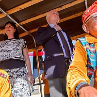 081415       Cable Hoover<br /> <br /> Republican Sen. John McCain of Arizona straightens his tie as he rides on float behind Navajo Codetalkers Bill Todelo, left, and Joe Vandever during the Codetalker Day parade Friday in Window Rock.