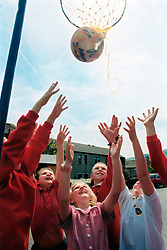 Schoolchildren playing bastketball or netball at primary school; Yorkshire UK