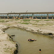 Shortly before the arrival of the monsoon, the flood plains around the Yamuna are dry. Some old ponds are used to play and wash.