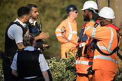 Police officers speak to an HS2 security guard holding an item which he had removed from the possessions of an anti-HS2 activist during tree felling works alongside the Grand Union Canal in connection with the HS2 high-speed rail link on 21 September 2020 in Harefield, United Kingdom. The police officers took possession of the item from the security guard, who had refused to return it to the activist, and returned it themselves to the activist on the opposite bank of the canal.