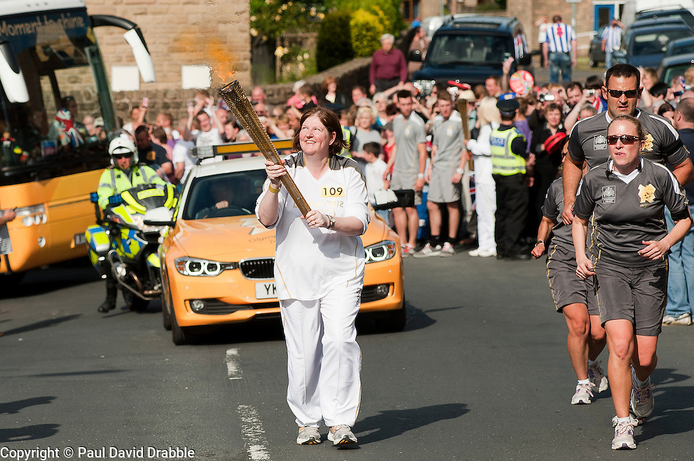 from the Chapeltown - Ecclesfield - Parson Cross section of the Journey.<br /> Locals take advantage of every possible vantage point as <br /> Torch bearer 109 Susan Prasad picks up flame and begins to make her way up Yew lane out of Ecclesfield and on towards Parson Cross<br /> 25 June 2012.<br /> Image © Paul David Drabble
