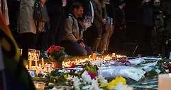 Church of St. Ann, Soho, London, June 13th 2016. Thousands of LGBT people and their friends converge on Old Compton Street in London's Soho to remember the fifty lives lost in the attack on gay bar Pulse in Orlando, Florida. PICTURED:  A man places a candle among dozens of others in the churchyard of the Church of St. Ann, Soho