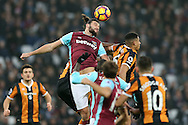 Andy Carroll of West Ham United jumps to head the ball over Curtis Davies of Hull City. Premier league match, West Ham Utd v Hull city at the London Stadium, Queen Elizabeth Olympic Park in London on Saturday 17th December 2016.<br /> pic by John Patrick Fletcher, Andrew Orchard sports photography.