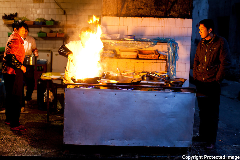 Flames shoot up as a cook stirfrys in an alley in Chengdu