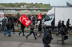 © Licensed to London News Pictures. 23/01/2016. Calais, France. A man holding a red flag of the New Anticapitalist Party (Nouveau Parti anticapitaliste) as a group of migrants storm towards the port of Calais in Northern France during a demonstration through the town centre of Calais, on the same day that Leader of the Labour Party JEREMY CORBYN visited the migrant camp known as the 'Jungle' . Photo credit: Ben Cawthra/LNP