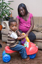 Heavily pregnant woman playing with her son,