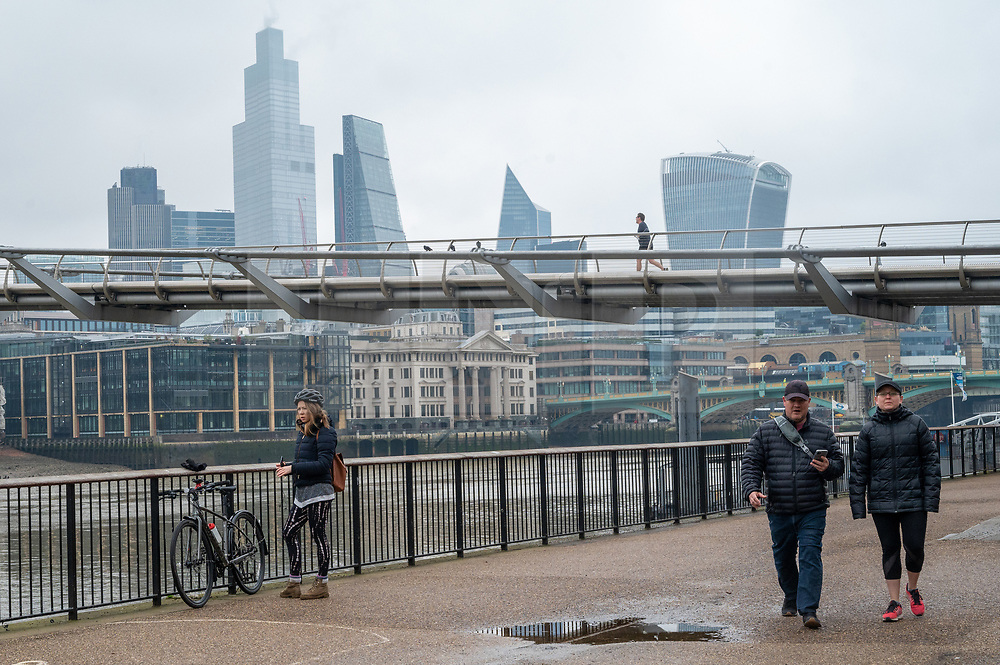 © Licensed to London News Pictures. 01/02/2021. London, UK. People walk along the River Thames near the Millennium Bridge. London is currently in Tier-4 advising people to stay at home. Today marked the 1st anniversary of first UK Covid-19 person. Since then, over, 100,000 people have died in the UK with the Covid-19 disease. Photo credit: Ray Tang/LNP