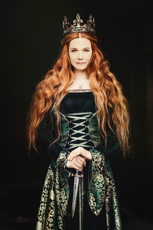 Portrait of a beautiful red-haired woman in green medieval dress