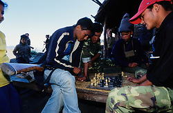 "Kusapani, 03 March 2005... Members of the 'Red Army' are playing chess. The Maoists have officially banned drinking alchool and playing cards. ""Alchool and cards can destroy a family. Women were often beaten by their drunken husbands, and people preferred to play cards rather than going to work "", a Maoist/journalist says."