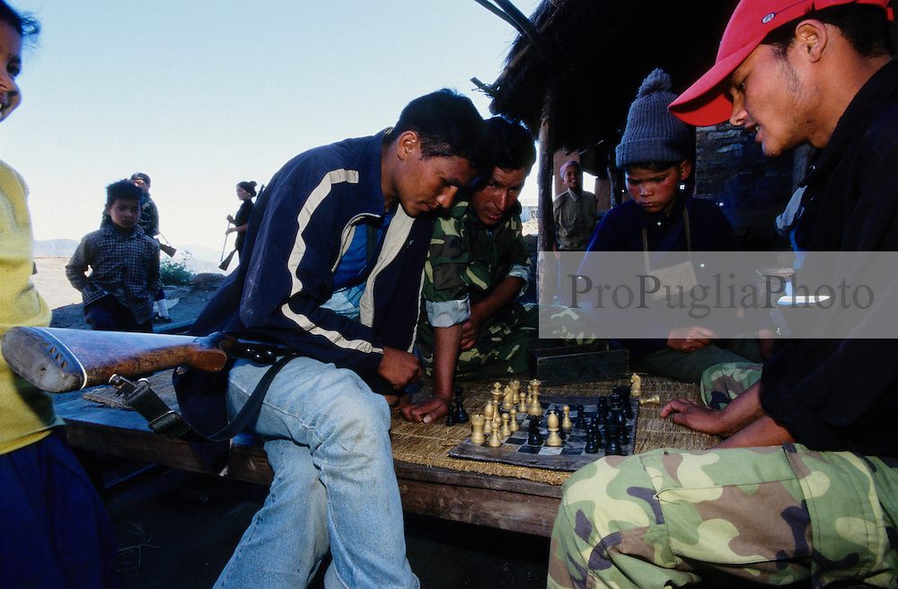 """Kusapani, 03 March 2005... Members of the 'Red Army' are playing chess. The Maoists have officially banned drinking alchool and playing cards. """"Alchool and cards can destroy a family. Women were often beaten by their drunken husbands, and people preferred to play cards rather than going to work """", a Maoist/journalist says."""