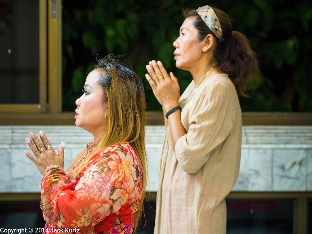 17 AUGUST 2014 - BANGKOK, THAILAND:        Women pray in the Vishnu temple in Bangkok during the celebration of Krishna Janmashtami. Krishna Janmashtami is the annual celebration of the birth of the Hindu deity Krishna, the eighth avatar of the Hindu god Vishnu. It is celebrated by Hindus in Thailand. There are about 53,000 Hindus in Thailand, most originally from India, but many Hindu deities are highly revered by Thai Buddhists and Hindu holy days are observed by many Thai Buddhists.   PHOTO BY JACK KURTZ