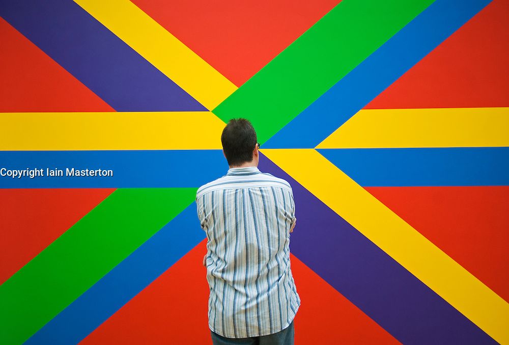 Man looking at abstract modern art painting in famous GemeenteMuseum in The Hague Holland