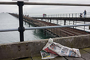 As small figures of people walk in the distance, pages of a crumpled newspaper lies on the floor on Southend Pier, the worlds longest at a mile and a quarter, at Southend-on-Sea, Essex. Southend-on-Sea is a seaside town on the north side of the Thames estuary 40 miles 64 km east of central London. In its heyday, the working class visited from the capital when train transport allowed them to enjoy its beaches and the worlds longest pier. Its splendour faded on the advent of package holidays to Spain etc.