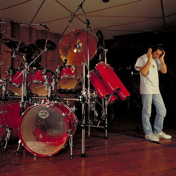 Simon Philips listening to his work. Red Tama Starclassic drum kit.