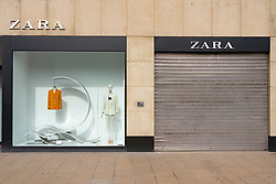 Edinburgh, Scotland, UK. 24 March, 2020.  Princes Street which is Edinburgh's main shopping street is very quiet. All shops and restaurants are closed with very few people venturing outside following the Government imposed lockdown today. Pictured; a closed Zara store. Iain Masterton/Alamy Live News