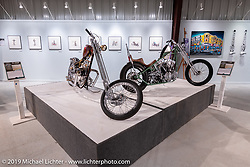 Bagger Nation's Paul Yaffe's Re-Cycled (L) custom 1964 Triumph Thunderbird 650 and Nick Pensebene's 3-Peat is a custom 1967 Shovelhead Chopper on view in the What's the Skinny Exhibition (2019 iteration of the Motorcycles as Art annual series) at the Sturgis Buffalo Chip during the Sturgis Black Hills Motorcycle Rally. SD, USA. Friday, August 9, 2019. Photography ©2019 Michael Lichter.