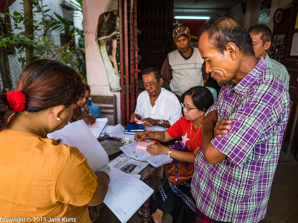 02 NOVEMBER 2015 - YANGON, MYANMAR: A Burmese voter (right, checked shirt) talks to NLD outreach workers because he couldn't find his name on voter rolls at a NLD campaign outreach office in North Okkalapa, a township in Yangon. Voter registration rolls were released Monday. Voters and party officials are double checking rolls to ensure accuracy.  National elections are scheduled for Sunday Nov. 8. The two principal parties are the National League for Democracy (NLD), the party of democracy icon and Nobel Peace Prize winner Aung San Suu Kyi, and the ruling Union Solidarity and Development Party (USDP), led by incumbent President Thein Sein. There are more than 30 parties campaigning for national and local offices.     PHOTO BY JACK KURTZ