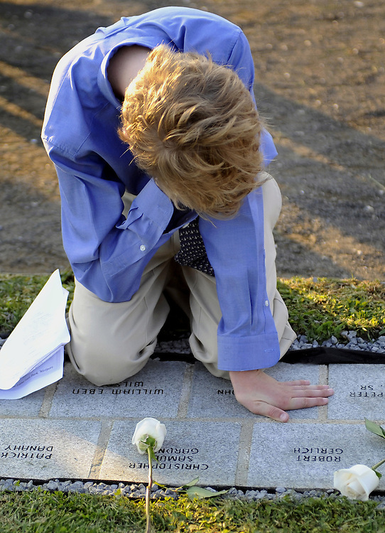 Christopher Gardner, 12, of Darien kneels on a memorial with his father's name  during a remembrance ceremony for Connecticut victims of the Sept. 11, 2001 terrorist attacks at Sherwood Island State Park in Westport, Conn., Tuesday, Sept. 7, 2010.  Gardner's father Christopher Samuel Gardner worked at the World trade center and was killed in the Sept. 11 attack.  (AP Photo/Jessica Hill)