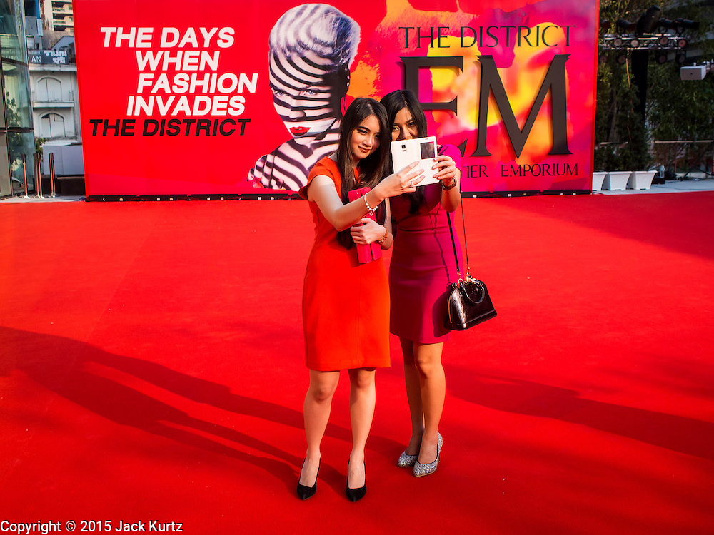 """27 MARCH 2015 - BANGKOK, THAILAND: Women pose for """"selfies"""" on the red carpet in front """"EmQuartier,"""" a new mall in Bangkok. """"EmQuartier"""" is across Sukhumvit Rd from Emporium. Both malls have the same corporate owner, The Mall Group, which reportedly spent 20Billion Thai Baht (about $600 million US) on the new mall and renovating the existing Emporium. EmQuartier and Emporium have about 450,000 square meters of retail, several hotels, numerous restaurants, movie theaters and the largest man made waterfall in Southeast Asia. EmQuartier celebrated its grand opening Friday, March 27.    PHOTO BY JACK KURTZ"""