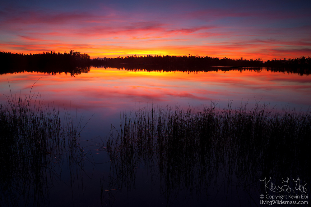 A stormy fall sunset is reflected in the waters of Cranberry Lake on the north end of Whidbey Island..