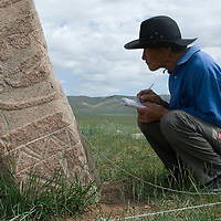 "Mongolian archaeologist Tovuudorj Sanjmyatov (""Sasha"") (MR) sketches carvings on a 2700+ year-old, bronze age deer stone monument at Ulaan Tolgai archaeological site near Lake Erkhel, north of Muren, Mongolia.   <br /> MS0702_060626_0161.NEF"