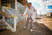 """24 JANUARY 2010 -- WENDEN, AZ:  Jose Montes, (CQ) a 14 year resident of Wenden, cleans the front of his home. During a break he said, """"This is a lot of work for one person."""" Wenden was slammed by its second 100 year flood in 10 years on Thursday night when water raced through Centennial Wash and into the small town in La Paz County west of Phoenix. Most of the town's residents were evacuated to Red Cross shelters in Salome, about 5 miles west of Wenden.    PHOTO BY JACK KURTZ"""