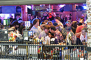 3/5/21 Oxford MS. Oxford, Mississippi, USA: March 5, 2021, Students of The University of Mississippi, aka, Ole Miss, party and enjoy a night out on the first Friday night after Governor Tate Reeves lifted the state wide mask mandate. The bars in downtown Oxford were packed with students shoulder to shoulder drinking and partying. Dr Fauci has stated that Mississippi and Texas residents should continue to abide by public health measures, including wearing masks and social distancing, even as Republican Governors have lifted all Covid-19 restrictions in Texas and Mississippi. Photo© Suzi Altman