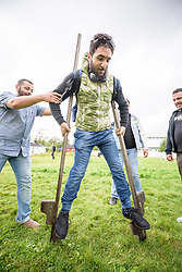 """13 August 2016, Norrbyskär, Umeå, Sweden: Obeida Mehmed, a Syrian refugee recently arrived in Sweden, practices walking on stilts, helped on by Adnan Al Mousa from Syria, during the Kul-Tur Fest (""""Culture Festival""""). The event, which attracted hundreds of people, set out to offer a meeting place for Swedish culture and new forms of cultural expression, and featured baking competitions, dance workshops, book discussions, fingernail painting and music, among other things."""