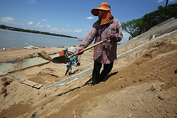 Workers on the embankment protection construction along the banks of the Mekong River in Stung Treng town, Stung Treng Province, Cambodia.
