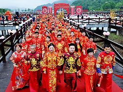 April 30, 2019 - Shangrao, China - Couples walk on the red carpet during the collective wedding ceremony in Dexing City, east China's Jiangxi Province. A collective wedding ceremony was held here on Tuesday, during which 70 pairs of couples, both newly-wed and elderly couples, took part and called for frugality. (Credit Image: © Xinhua via ZUMA Wire)