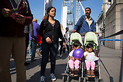 Tourists pushing twins in a pram near to the London Eye, one of the biggest draws for tourism down on the Southbank. The South Bank is a significant arts and entertainment district, and home to an endless list of activities for Londoners, visitors and tourists alike.