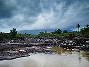 29 JANUARY 2018 - GUINOBATAN, ALBAY, PHILIPPINES: A river in the lava bed of Mayon volcano. The volcano's eruptions have loosened rock and gravel on the mountain, increasing the chances for rockslides and floods to communities near rivers coming down the mountain. Mayon volcano's eruptions continued Monday. At last count, more 80,000 people have been evacuated from their homes of the slopes of the volcano and are crowded into shelters in communities outside of the danger zone.    PHOTO BY JACK KURTZ