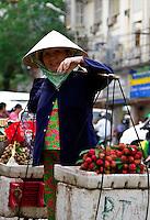 A street vendor with  rambutans.