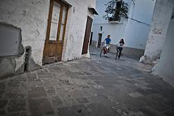 Siamo in Puglia, a Specchia cittadina della provincia di Lecce, situato a circa 60 Km a sud del capoluogo di provincia..Si presenta come un paese tranquillo ma vivo..Le strade luminose e pulite presentano una pavimentazione a lastroni antichi..Il centro storico è un'area pedonale ed è spesso scenario di manifestazioni sacre e culturali..La gente è gentile ed ospitale e si è lasciata fotografare con tranquillità, facendosi riprendere nel loro fare quotidiano, quasi fosse abituata ad essere fotografata..Quest'area del Salento è meta di un turismo alla ricerca della tranquillità e della cultura; cultura intesa anche come eno-gastronomia, e soprattutto cultura volta al rispetto della natura..I turisti in cerca di aria sana, pulita, vengono nei paesini dell'entroterra salentino, lontani dalla città e dallo smog..Appena entrati in paese ci si ritrova una piazzetta moderna, molto ben concepita architettonicamente, sulla quale si affacciano anche palazzi di età più antica, probabilmente dell'inizio del '900...La piazza e le strade nei dintorni sono animate dalla popolazione, che approfitta del primo fresco del pomeriggio per uscire a stare in compagnia..Gente del posto, anziani in prima linea vivono la piazza, ragazzi passeggiano e visitano il palazzo e le attività commerciali..Passeggini e biciclette percorrono le strette vie del borgo, qua e là la gente fa capolino e si appresta a uscire a ritirare i panni o a far visita al vicino...I turisti visitano le vie del borgo, quasi perdendosi nei viottoli tortuosi che ora si arrampicano verso l'alto, altri con ripide discese vanno verso la campagna dei dintorni..Lunghe sono le passeggiate in bicicletta, da fare sia in paese sia nei percorsi ciclo-turistici delle campagne assolate di Specchia.