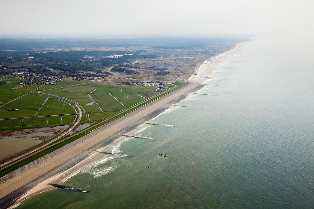 Nederland, Noord-Holland, Gemeente Schoorl, 28-04-2010; Hondsbossche zeewering gezien naar het zuiden, Schoorlse duinen aan de horizon. Links van de zeedijk de Vereenigde Harger- en Pettemerpolder. De dijk is aangelegd als zeewering nadat de oorsrponkelijke duinen weggeslagen waren. Door erosie kalven de duinen langs de kust steeds verder af, de dijk steekt daardoor steeds meer uit in zee..Hondsbossche seawall seen to the south, left of the seawall and the United Harger Pettemer Polder. The dike was built as a seawall after the primal dunes were washed away. Because of erosion the dunes decrease in size, therefore the sewall sticks more and more out into the sea..luchtfoto (toeslag), aerial photo (additional fee required).foto/photo Siebe Swart